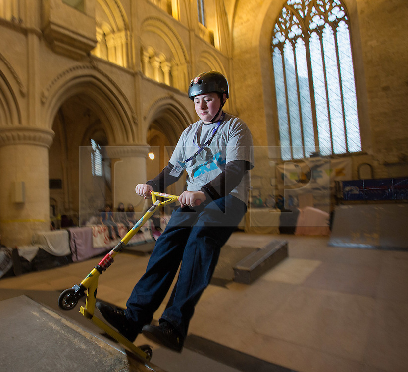 """© Licensed to London News Pictures 15/02/2017, Malmesbury, UK. The """"Malmesbury Abbey Skate"""" now in its's 9th year, where the interior of the 12th century abbey in Malmesbury, Wiltshire is turned into a skate park for 3 days during the February half term. Pictured here: 15 year old George Mcgrory on his scooter.<br /> Photo Credit : Stephen Shepherd/LNP"""