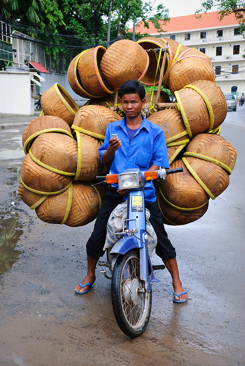 A Cambodian man operates his mobile phone while sitting on his motorbike loaded with woven baskets. (Phnom Penh, Cambodia - June 25, 2007)