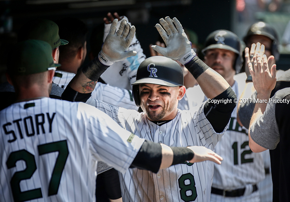 SHOT 5/28/17 1:12:27 PM - The Colorado Rockies Gerardo Parra #8 celebrates with teammates in the dugout after hitting a three-run homer against the St. Louis Cardinals during their regular season MLB game at Coors Field in Denver, Co. The Rockies won the game 8-4. (Photo by Marc Piscotty / © 2017)