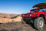 An H1 Hummer parked on a sandstone hilltop over looking the Colorado River on a 4x4 tour on the Hell's Revenge Trail in the Sandflats Recreation Area near Moab, Utah.