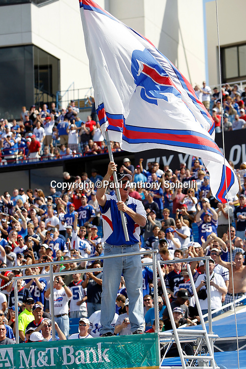 Former Buffalo Bills quarterback Jim Kelly waves a team flag during player introductions during the NFL week 3 football game against the New England Patriots on Sunday, September 25, 2011 in Orchard Park, New York. The Bills won the game 34-31. ©Paul Anthony Spinelli