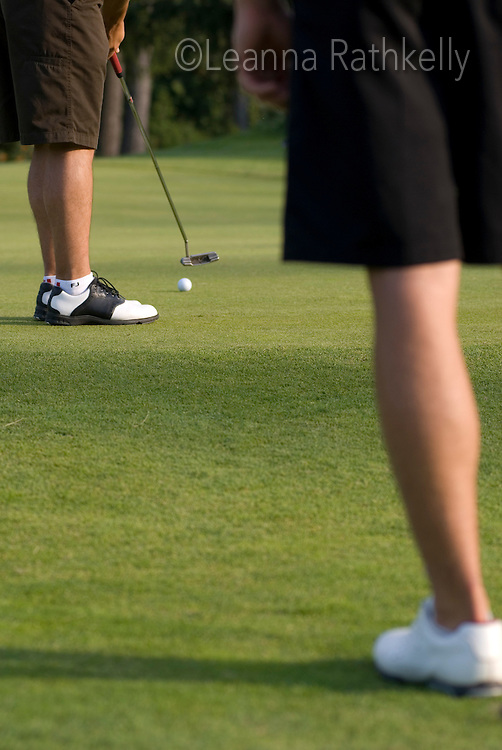 Close shot of a golfer just about to sink a putt on the golf green, with another golfer's legs in the foreground. Whistler Golf Course, Whistler, BC Canada.