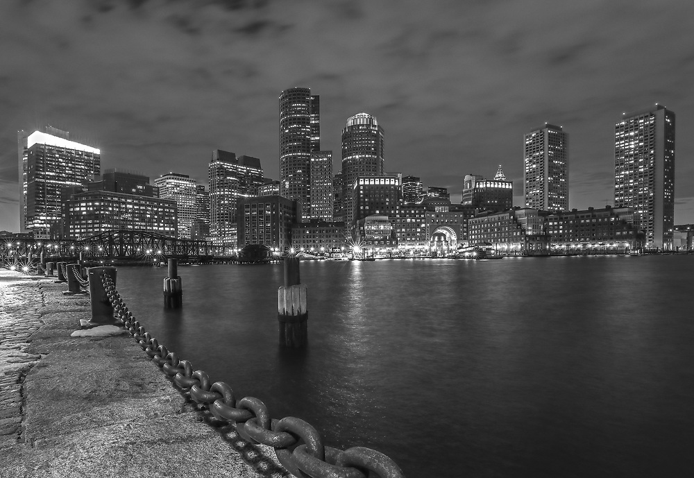 Boston Harbor skyline black and white photography from New England Photography Guild member and award winning fine art photographer Juergen Roth showing Boston Financial Waterfront District landmarks such as One International Place, Boston Harbor Hotel, Independence Wharf, Department of Homeland Security building, and other structures along Rowes Wharf photographed on a beautiful winter sunset evening. The last light was painting the cloudscape in fire red hues and the long exposure time ensured the intentional blurry cloud movement. <br />