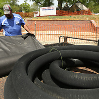 Adrian Sanchez, an employee with Tupelo Parks and Recreation, unrolls landscaping felt for a drainage and irrigation project being installed on the west side of the walking track at Robins Field on Thursday.