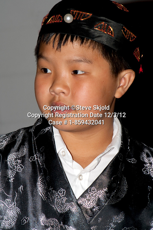 Asian American boy age 9 wearing ceremonial robe at Minnesota history presentation. Horace Mann School. St Paul Minnesota MN USA