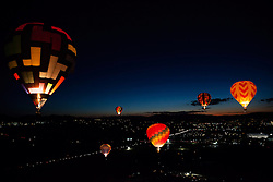 """Dawn Patrol 9"" - Photograph of glowing hot air balloons flying for the Dawn Patrol at the 2012 Great Reno Balloon Race. Photographed from a hot air balloon."