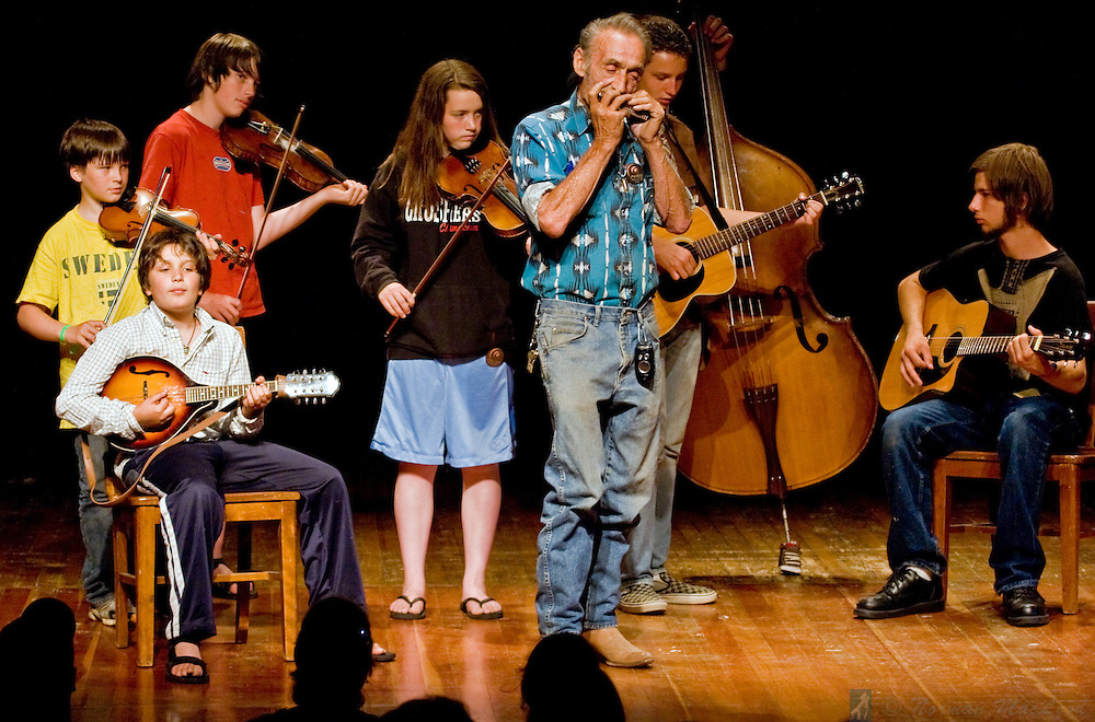 Young musicians onstage with Andy Mackie at the Festival of American Fiddle Tunes participants' concert