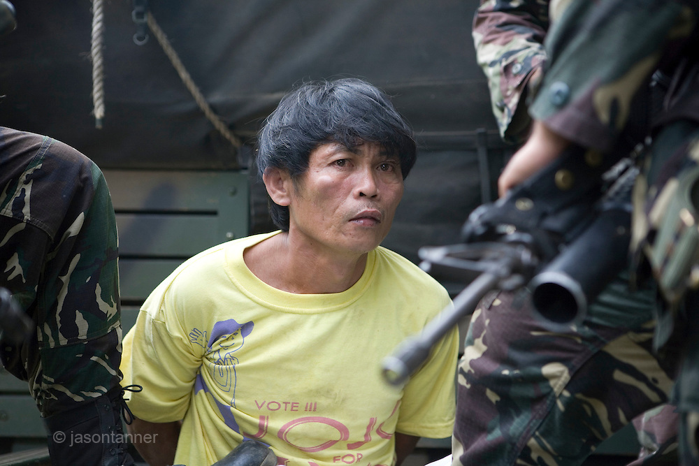 Miguelito Maglangit, an MILF collaborator is detained just outside the town of Iligan, North of Cotabato in Mindanao, Philippines. He was identified by neighbours of leading the assault by members of the MILF rebels on the towns of Barangay Bantar and Libertat on 18th August 2008...If found guilty he will be executed by the military...Renegade members of the MILF reportedly under the leadership and direction of Commander Bravo in North Cotabato launched a series of attacks on local villages resulting in the death of 21 civilians and a further 2 military personnel murdered when their vehicle was ambushed outside the town of Barangay Bantor...The first attack occurred at approx 04.00am local time with the ambush on the local vehicle, MILF rebels then moved through the village fo Barangay Bantor burning15 houses and killing 7 unarmed civilians. 35 members of the village were forcibly abducted and taken as hostages into the surrounding forest. ..At approx 04.30am the MILF attacked the town of Barangay Libertat, destroying up to homes and killing a further 14 civilians...Violence began after a deal to expand the Muslim autonomous zone was blocked by the Philippines Supreme Court. Rebels from the Moro Islamic Liberation Front (MILF) occupied some 15 villages in the region triggering a retaliatory assault by the Philippine army involving heavy artillery and air support..
