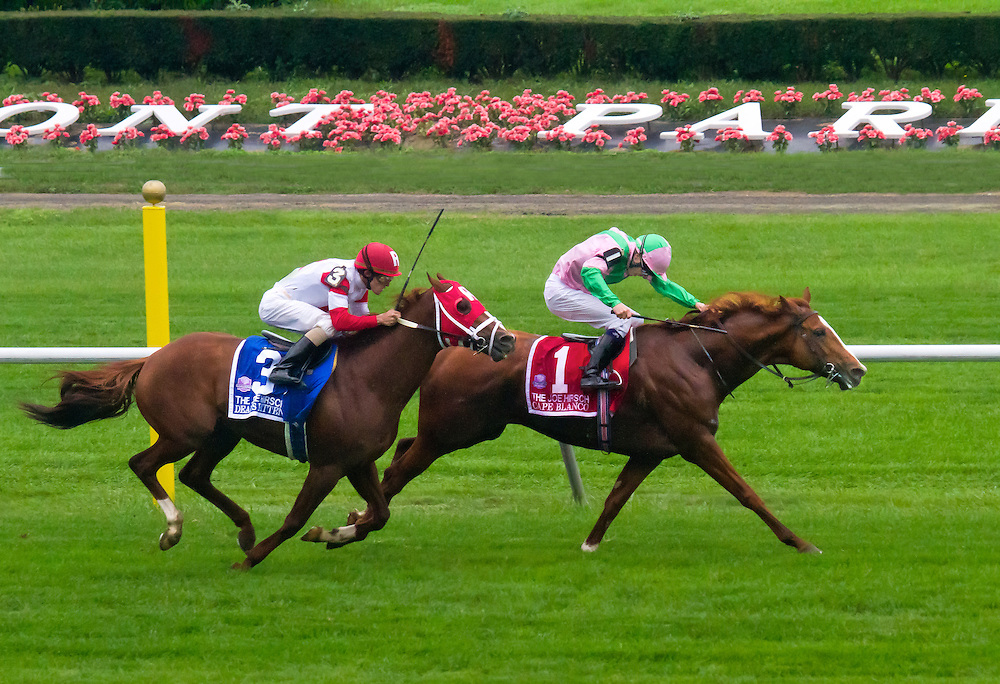 "Here again in deep stretch, ""Cape Blanco"" jockey Jim Spencer is still working furiously on him to hold on against the late charge of ""Dean's Kitten"", who is fast closing the gap even more. 2011"