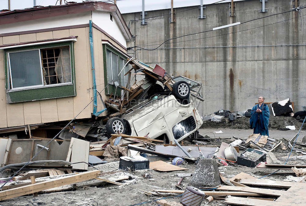 Buddhist monk Sokan Obara, 28, from Morioka, offers prayer for the deceased outside a home wrecked by the March 11 tsunamis in Ofunato, Iwate Prefecture, Japan on April 3, 2011. <br /> Photographer: Robert Gilhooly