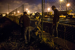 **Images taken on the evening of the 11th of August** © Licensed to London News Pictures. 11/08/2015. Calais, France. A group of four  migrants enter the train tracks to the Eurotunnel terminal underneath a fence late at night at Frethun near Calais, northern France. . Photo credit: Ben Cawthra/LNP