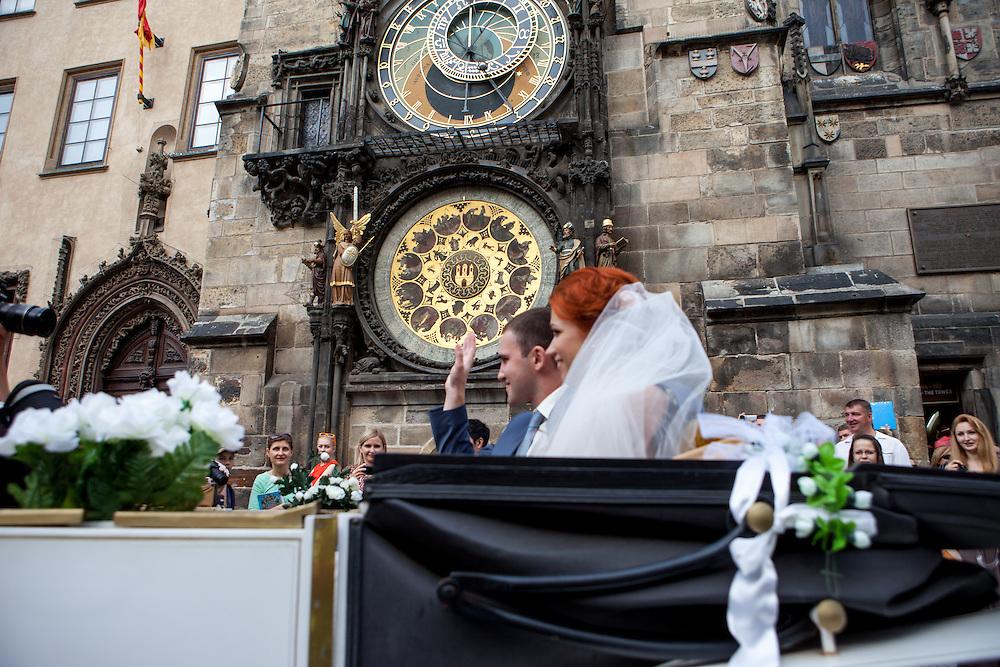 Ein russisches Hochzeitspaar unter der Astronomischen Uhr auf dem , Altstaedter Ring in Prag.