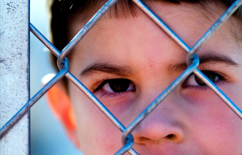 041707      Brian Leddy.Brady Scaggari, 4, peers watches the Gallup baseball ball game against West Mesa through the fence on Tuesday. The 4-year-old came to watch his uncles coach the baseball team.