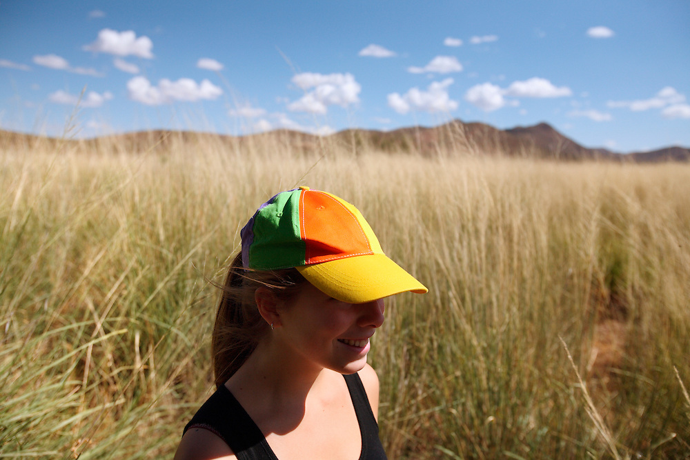A girl in a colorful hat stands in a field of wild grass under a cloudy sky.