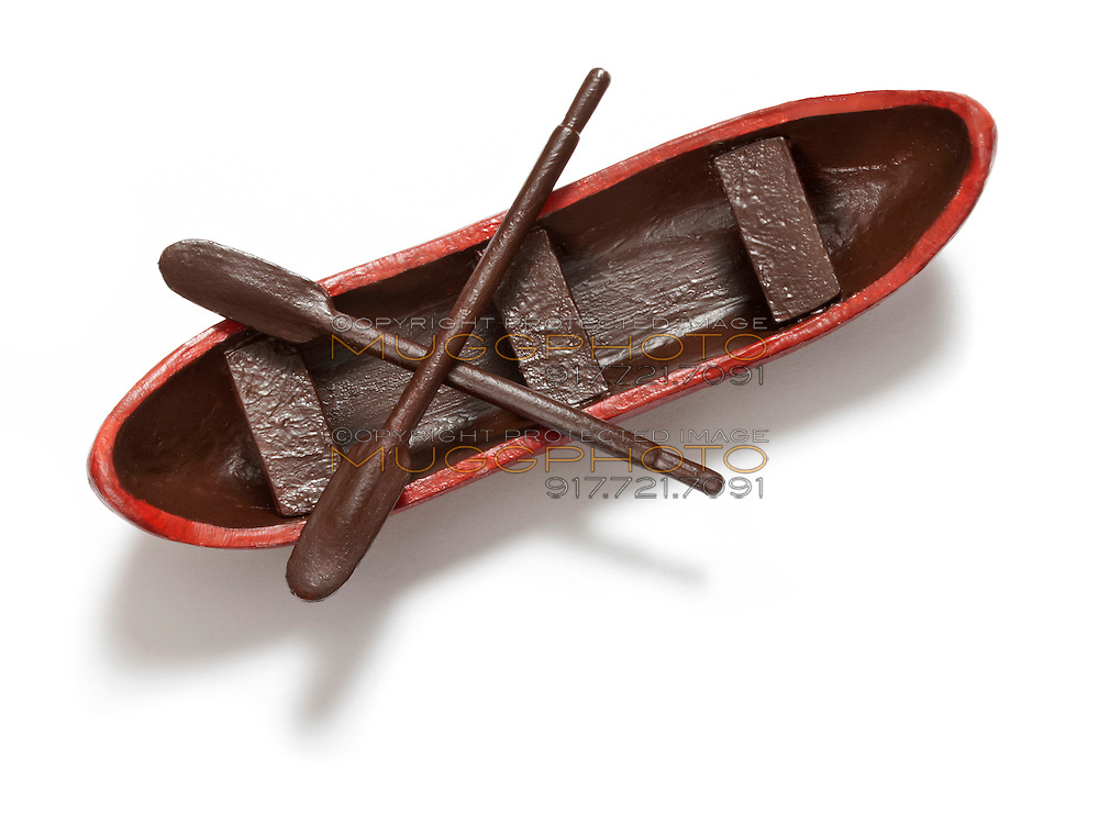 Toy canoe with paddles on white background