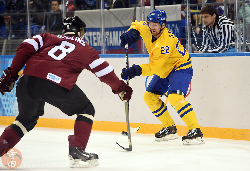 Feb 15, 2014; Sochi, RUSSIA; Sweden forward Daniel Sedin (22) handles the puck against Latvia defenseman Sandis Ozolins (8) in a men's preliminary round ice hockey game during the Sochi 2014 Olympic Winter Games at Shayba Arena.