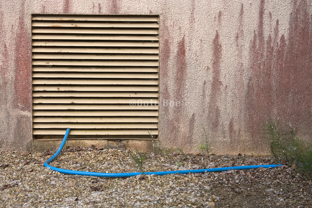 water hose coming outside through grill in the wall