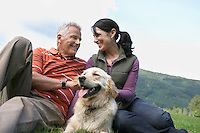 Couple and golden retriever resting on grass