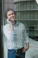 Man using mobile phone standing by window