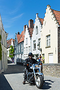 Motorcyclist and painted houses with crow-stepped gables  by Groenerei (green Canal) in Bruges, Belgium
