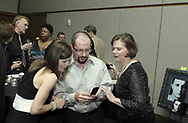 Gloria (back left) and Stuart McDowell talk with Nan-C Moss as Michelle Zimmerman (front left) reacts to something on a cell phone in the Piano Lounge at the 21st birthday party of the Human Race Theatre Company in Sinclair's Ponitz Center, Saturday night, April 28th.