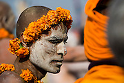 A Naga Sadhu is covered in ash and decorated with marigold at the Kumbh Mela.