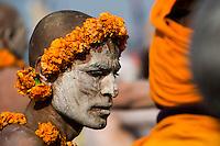 A Naga Sadhu is covered in ash and decorated with marigold at the Kumbh Mela.