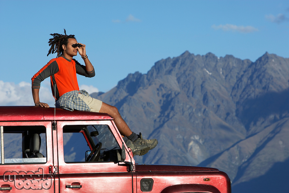 Man shading eyes on top of jeep near mountains