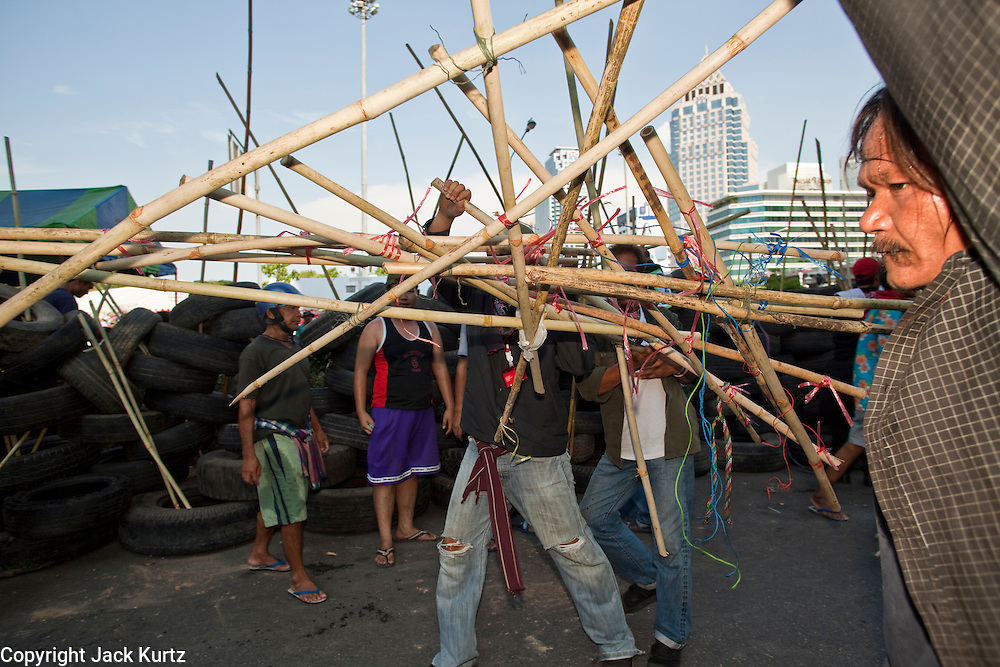 Apr. 30 - BANGKOK, THAILAND: Red Shirts move a bamboo rampart to a new barricade in the Sala Daeng intersection in Bangkok. The Red Shirts moved one of their barricades in the Sala Daeng Intersection in Bangkok Friday In one of the first positive moves to take place since the Red Shirts occupied central Bangkok in early April. The barricade was moved far enough back to open one lane of traffic on  Ratchadamri Street to allow ambulance access to King Chulalongkorn Memorial Hospital, a large hospital at the intersection. Many of the patients in the hospital have been moved to other hospitals because a group of Red Shirts entered the hospital Thursday looking for Thai security personnel, who were not in the hospital. The stand off between the Red Shirts and the government enters its third month in May. The Red Shirts continue to call for Thai Prime Minister Abhisit Vejjajiva to step down and dissolve parliament and demand the return of ousted Prime Minister Thaksin Shinawatra.   PHOTO BY JACK KURTZ