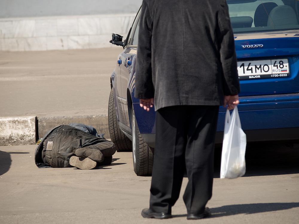 Obdachloser Mann schl&auml;ft auf einem Parkplatz zwischen Autos auf der gegen&uuml;berliegenden Stra&szlig;enseite des Kasaner Bahnhofs (Kasanski woksal) welcher einer der neun Bahnh&ouml;fe in Moskau ist. Er liegt am Komsomolskaja-Platz, in unmittelbarer N&auml;he zum Jaroslawler und dem Leningrader Bahnhof, und ist bis heute einer der gr&ouml;&szlig;ten Bahnh&ouml;fe der russischen Hauptstadt. <br /> <br /> Homeless person is sleeping on a parking place in between cars on the opposite site of the Kazansky Rail Terminal (Kazansky vokzal) which is one of eight rail terminals in Moscow, situated on the Komsomolskaya Square, across the square from the Leningradsky and Yaroslavsky terminals.