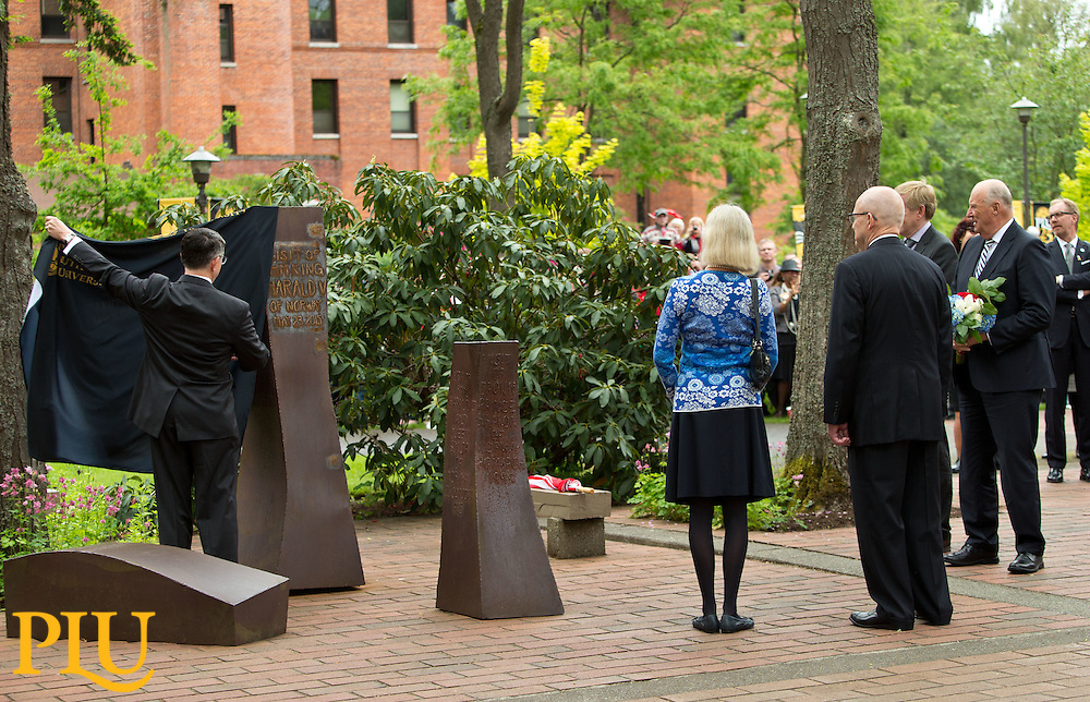 President Thomas Krise unveils the inscription on the rune commemorating the visit of HM King Harald V of Norway to Pacific Lutheran University on Saturday, May 23, 2015. Later His Majesty delivered the commencement address and received an honorary degree. (Photo: John Froschauer/PLU)