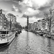View on one of the Unesco world heritage city canals (Prinsengracht) of Amsterdam whit The Westerkerk Church in the background, The Netherlands.