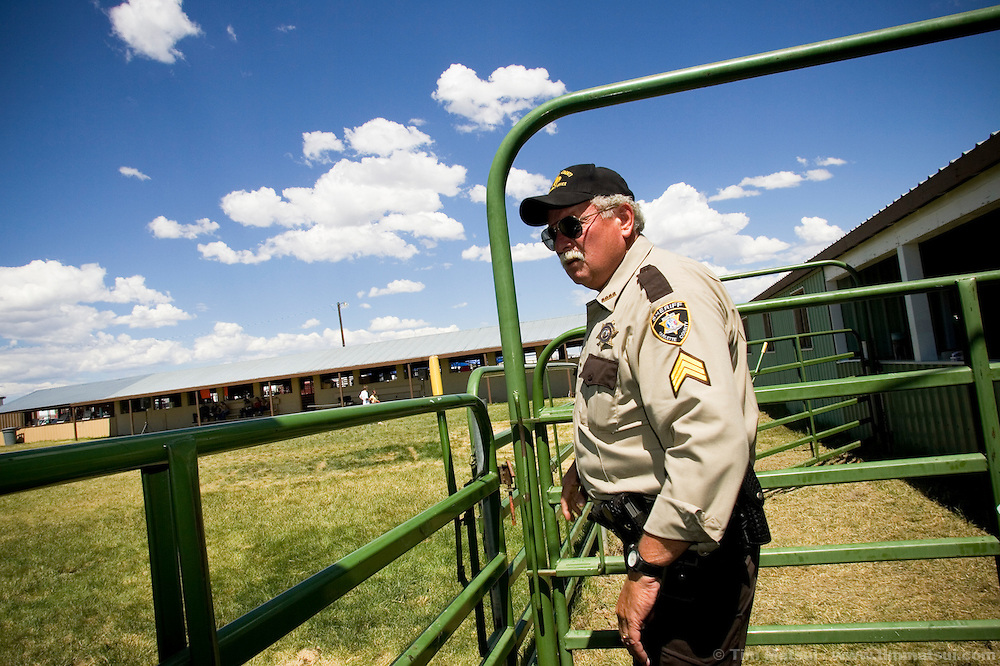 BIG PINEY, WY - Patrol Sergean Mike Peterson, at the Sublette County fair in Big Piney, Wy. on August 6, 2005. The Sheriff's department is struggling with retention of officers as the younger officers who are less committed to the profession struggle with a lack of affordable housing in the community. With an average deputy's salary at about $40,000 a year several on the force have been lured away by gas field wages. A starting roughneck with performance and safety bonuses can earn upwards of $400 a day while an engineer running a well logging truck can earn roughly $140,000 a year. Sheriff Bardin's son works the gas fields and, Bardin says, almost definitely earns more than his father the county sheriff.