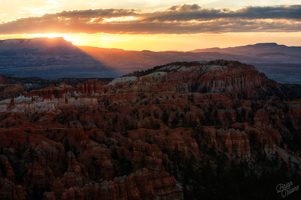 Particles of light cross the threshold of the distant ridge, bringing a new day to Bryce Canyon's towering hoodoos.