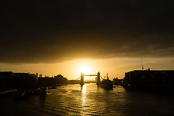 © Licensed to London News Pictures. 17/10/2014. London, UK. Black clouds soon appear just after an orange sunrise behind Tower Bridge in London this morning. Photo credit : Vickie Flores/LNP