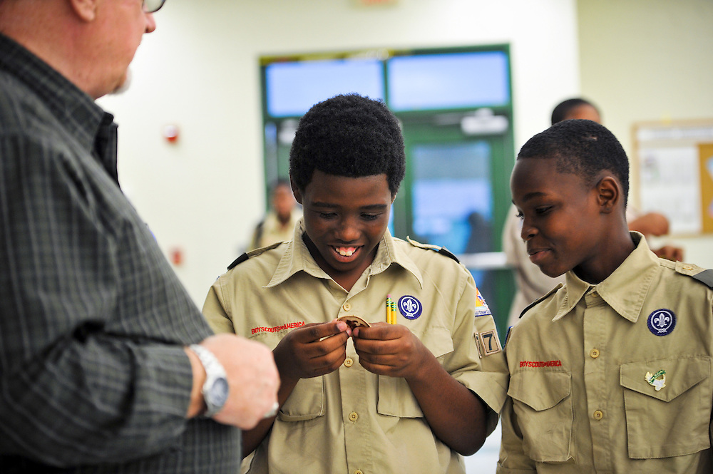 Assistant Scoutmaster Donald Lucy, who's also an assistant professor at Indian River State College, awards Lenzel Robinson, left, and Demetric Wilson the troop's first Boy Scout patches at Dan McCarty Middle School in Fort Pierce on Feb. 12, 2014. (XAVIER MASCAREÑAS/TREASURE COAST NEWSPAPERS)