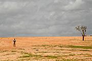 A boy stands in a desert like landscape in a refugee camp in Touloum in Tchad, close to the sudanese border. However, more than 23.000 refugees from Darfur, mainly women and children, live in the camp. The conflict in Darfur with its ethnic cleansing is also a direct result of climate change. Farmers and herders are pitted against each other over diminishing  pasture and resources. The barren land is taken over by the Sahara desert, which has expanded 60 miles over the last 40 years. Rainfall is down by 16-30 percent. Crops are failing. With further global warming, conflicts like Darfur are likely to be repeated on even larger scale.