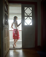Woman standing in open door  Looking Out back view