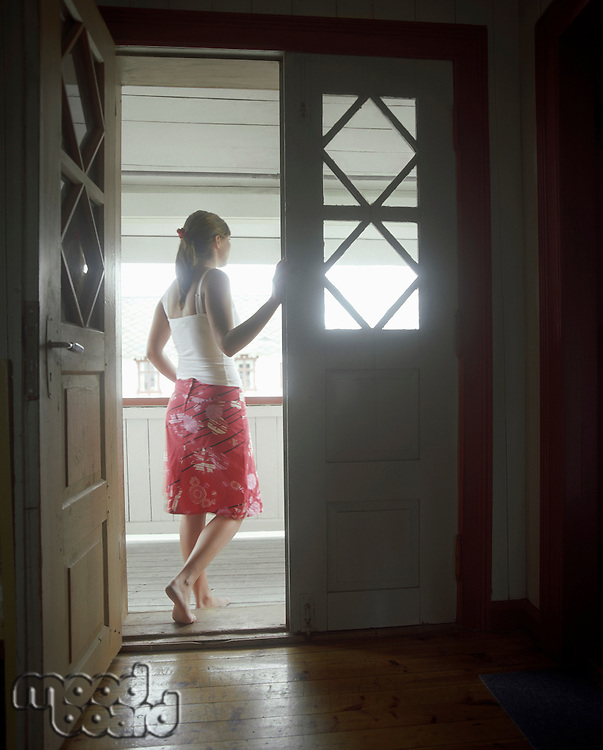 Woman standing in open door  Looking Out back view