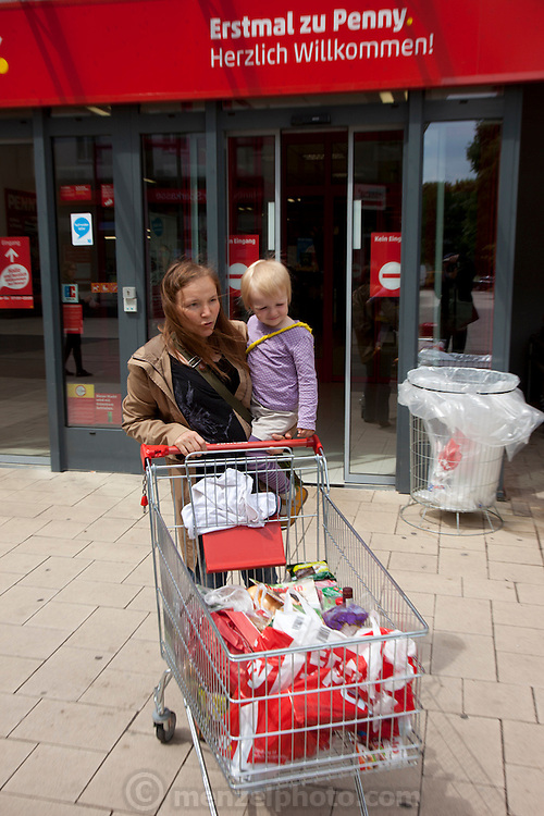 Astrid Holmann and her daughter Lillith in Hamburg, Germany shopping in the Penny supermarket. They were photographed for the Hungry Planet: What I Eat project with a week's worth of food in June. Model Released.