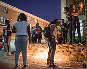 Baltimore, Maryland - April 21, 2015: After a vigil-turned-protest march for Freddie Gray people lit candles at his memorial site in West Baltimore Tuesday April 21, 2015. The memorial site marks the location where Gray was apprehended and allegedly injured by police over a week ago. On the day of his arrest he went in to a coma from injures sustained in the back of a police van. His spinal cord was 80% severed. He died last Sunday.<br /> <br /> CREDIT: Matt Roth for The New York Times<br /> Assignment ID: 30173645A