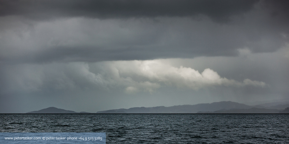 Looking south east along Tamaki Strait with the mainland to right and the distinctive triangular shape of Pakihi Island to the extreme left. A cloudy and overcast day. Hauraki Gulf, Auckland, New Zealand.