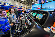Two boys have a go on a sophisticated Raymarine navigation simulator which has been connected to a real driving console from a Sunseeker Predator. The CWM FX London Boat Show, taking place 09-18 January 2015 at the ExCel Centre, Docklands, London. 09 Jan 2015.
