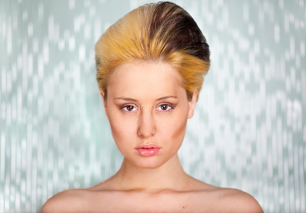 Blonde with unique hairdo in front of green backdrop