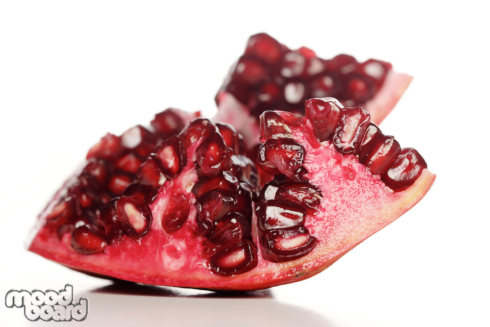 Close-up of pomegranate seeds on white background
