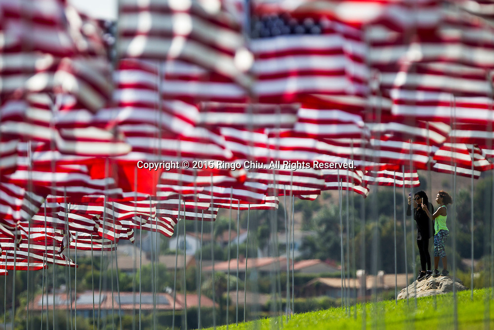 People take pictures amongst 3,000 US flags are displayed at Pepperdine University to mark the 14th anniversary of the 9/11 terror attack, September 10, 2015 in Malibu, California.  Photo by Ringo Chiu/PHOTOFORMULA.com)