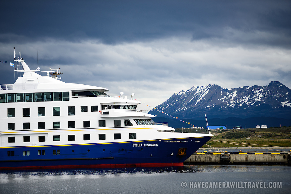 The Stella Australis, a cruise ship operated by Patagonia vacations that tours Southern Chile and Patagonia, is docked at Ushuaia Port in Ushuaia, Argentina. The snow-capped mountains in the distance are across the Beagle Channel in Chile.