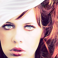 Portrait headshot of a red-haired girl in her early 20s looking youthful and like a doll