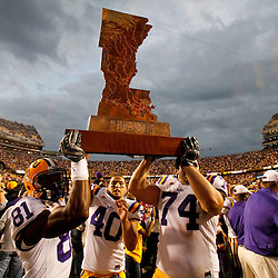 November 25, 2011; Baton Rouge, LA, USA;  LSU Tigers wide receiver Armand Williams (81), safety Rockey Duplessis (40) and guard Josh Williford (74) carry The Boot trophy following a win over the Arkansas Razorbacks at Tiger Stadium. LSU defeated Arkansas 41-17. Mandatory Credit: Derick E. Hingle-US PRESSWIRE