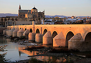 Roman bridge spanning river Rio Guadalquivir with Mezquita buildings, Cordoba, Spain
